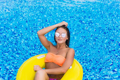Fashion photo of sexy beautiful Girl in yellow top and sunglasses relaxing floating on inflatable ring. Outdoors lifestyle portrai. Fashion photo of sexy Royalty Free Stock Photography