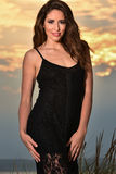Fashion photo of glamour model in black lace dress posing pretty on the beach. Royalty Free Stock Photos