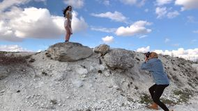 Fashion photo shoot Outdoors. Fashion photo shoot in a beautiful place against the sky with white clouds. A girl in fashionable clothes from a transparent bag stock footage