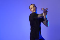 Fashion photo shoot of sport fit attractive man making arm stretch, tattooed hands, hipster look. Color flash studio light. Royalty Free Stock Images