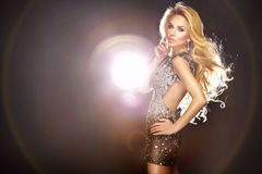 Beautiful sexy woman dancing in shining dress. Long curly blonde. Fashion photo of young beautiful dancing woman with long flowing hair and shining dress Royalty Free Stock Images