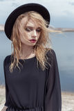 Fashion photo of young beautiful sexy girl with wet hair in a black hat and a black cotton dress with beautiful bright makeup Stock Photography