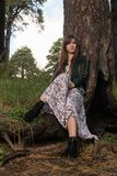 Fashion photo of young beautiful woman posing in forest near big tree Royalty Free Stock Photography