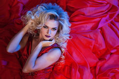 Fashion photo of young magnificent woman in red dress. Studio portrait Royalty Free Stock Images
