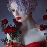 Fashion photo of young magnificent woman with red roses. Textured background. Stock Photography