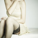 Fashion photo young sexual woman sitting on a sofa Royalty Free Stock Images
