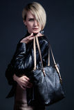 Fashion photo of young stylish woman in leather jucket with blac. K leather bag Royalty Free Stock Image