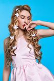Fashion photo of young woman against blue background wearing pink dress and hair pins look like butterflies. Close-up portrait of young woman posing against blue royalty free stock photography