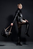 Fashion photo of young woman in leather jucket, leather skirt an. D bag Stock Image