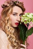 Fashion photo of young woman on pink background wearing flower wreath with flower near her face. Close-up beauty portrait of young woman wearing flower wreath royalty free stock photography