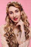 Fashion photo of young woman on pink background wearing gold diadem. Close-up beauty portrait of young woman wearing gold diadem with red lips with hands near royalty free stock photos