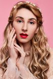 Fashion photo of young woman on pink background wearing gold diadem. Close-up beauty portrait of young woman wearing gold diadem with red lips with hands near royalty free stock photography