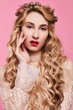 Fashion photo of young woman on pink background wearing gold diadem. Close-up beauty portrait of young woman wearing gold diadem with red lips with hands near stock photos