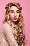 Fashion photo of young woman on pink background wearing gold diadem. Close-up beauty portrait of young woman wearing gold diadem with red lips with hands near royalty free stock photo