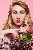 Fashion photo of young woman on pink background wearing gold diadem with flowers near her face. Close-up beauty portrait of young woman wearing gold diadem with stock photography