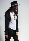 Fashion photo of young woman in trendy cardigan, black jeans and. Hat. Vintage necklace on the neck Stock Photo