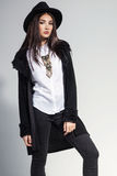 Fashion photo of young woman in trendy cardigan, black jeans and. Hat. Vintage necklace on the neck Royalty Free Stock Photography