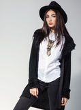 Fashion photo of young woman in trendy cardigan, black jeans and. Hat. Vintage necklace on the neck Stock Photography