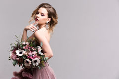 Fashion photo of young woman. Woman posing in pink dress. Studio. royalty free stock images