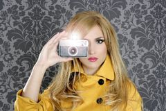 Fashion photographer retro camera reporter woman. Vintage wallpaper yellow coat Stock Images