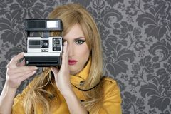 Fashion photographer retro camera reporter woman. Vintage wallpaper yellow coat Royalty Free Stock Photo
