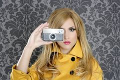 Fashion photographer retro camera reporter woman. Vintage wallpaper yellow coat Royalty Free Stock Photography