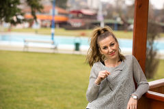 Fashion picture of a young beautiful woman leaned against wooden gazebo Royalty Free Stock Photo