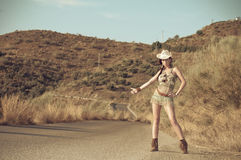 Fashion pictures of a sexy woman. Wearing cowgirl clothes hitchhiking Stock Photos