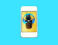 Fashion pineapple on screen smartphone over colorful blue royalty free stock image