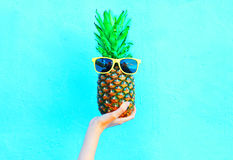 Fashion pineapple with sunglasses on blue background, hand ananas stock photography