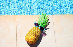 Fashion pineapple with sunglasses, blue water pool background, summer holidays,