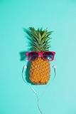 Fashion pineapple with sunglasses and headphones listens to musi Royalty Free Stock Image