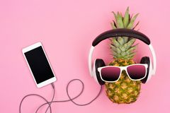 Fashion pineapple with sunglasses and headphones over pink Royalty Free Stock Photography