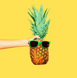 Fashion pineapple with sunglasses on yellow, hand holding ananas Stock Photos