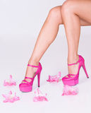 Fashion pink high heels and flowers. Woman feet wearing fashion pink high heels surrounded with flowers Royalty Free Stock Image