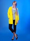 Fashion portrain of blond woman in trendy yellow jacket over blu Stock Image