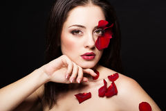 Fashion portrair of woman with rose petals on her face. Fashion portrair of woman with rose petals Royalty Free Stock Photography