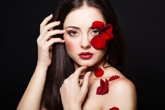 Fashion portrair of woman with rose petals on her face. Fashion portrair of woman with rose petals Royalty Free Stock Photo