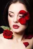 Fashion portrair of woman with rose petals on her face. Fashion portrair of woman with rose petals Royalty Free Stock Image