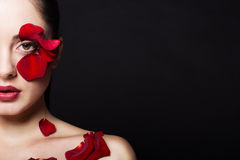 Fashion portrair of woman with rose petals on her face. Fashion portrair of woman with rose petals Stock Image