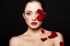 Fashion portrair of woman with rose petals on her face. Fashion portrair of woman with rose petals Stock Photo