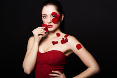 Fashion portrair of woman with rose petals on her face Stock Images