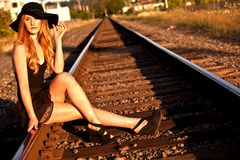 Fashion portrait. Young caucasian female model posing on railroad tracks with a large black hat Stock Photos