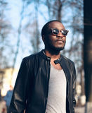 Fashion portrait african man wearing sunglasses, black rock leather jacket on street royalty free stock photo