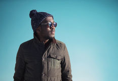Fashion portrait african man wearing sunglasses, jacket, knitted hat in winter day over blue sky background. Empty copy space Royalty Free Stock Photos