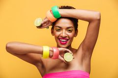 Fashion portrait of afro american woman wearing trendy accessories posing on camera with two parts of fresh ripe lemon in hands i. Solated over yellow wall stock photo