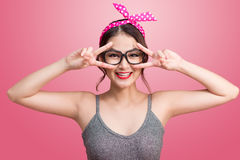 Fashion portrait of asian girl with sunglasses standing on pink. Background stock photography