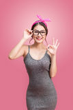 Fashion portrait of asian girl with sunglasses standing on pink. Background stock images