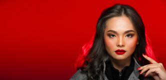 Fashion portrait of Asian Gray curl hair woman with strong color. Red lips, studio lighting red reddish background copy space, girl wear overcoat in winter royalty free stock photo
