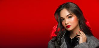 Fashion portrait of Asian Gray curl hair woman with strong color. Red lips, studio lighting red reddish background copy space, girl wear overcoat in winter stock photography